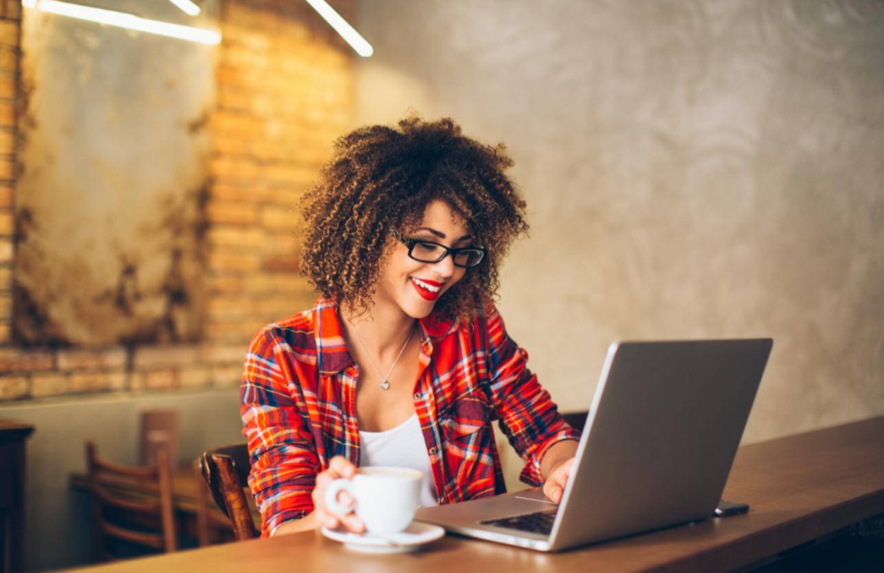 Afroamerikanische Frau mit Laptop im Café